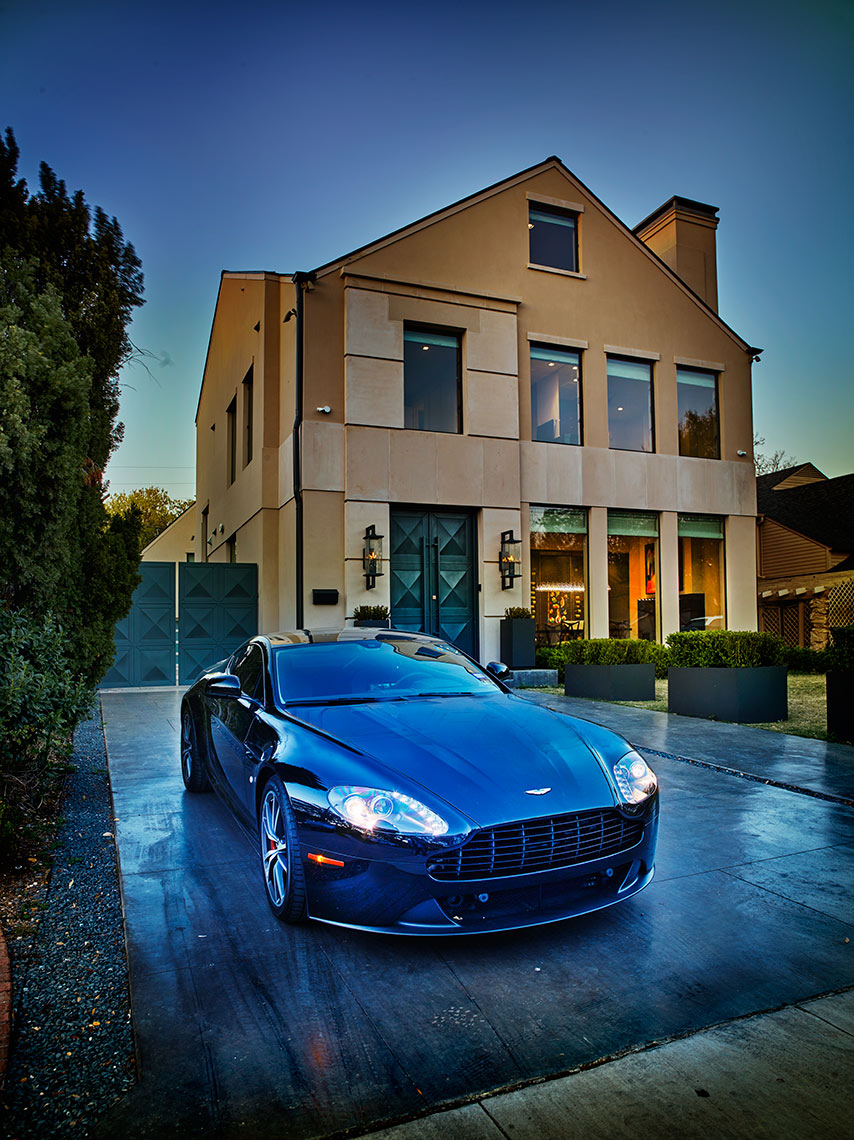 Aston Martin in front of modern home exterior in Highland Park, TX